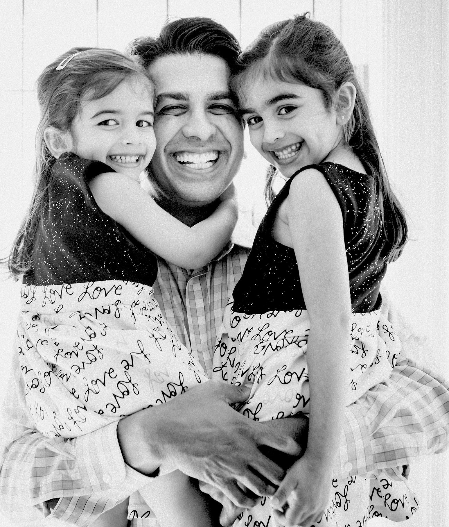 "Man in checkered button down shirt has a huge smile as he holds up two young toddlers aged girls in his arms. The girls are wearing identical dresses with a black top and white skirt with ""love"" printed all over it."