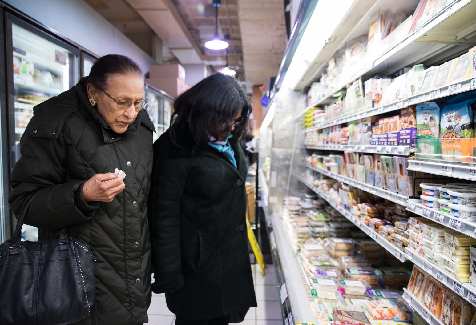 Woman and older woman both look at food selections in a supermarket aisle.