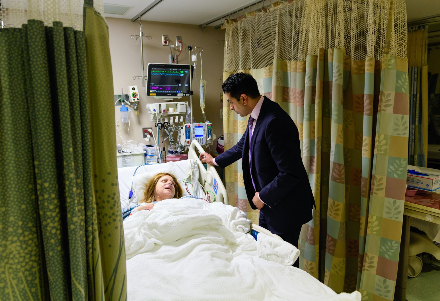 Man in blue suit stands in a hospital room looking over a woman laying in a hospital bed. She is hooked up to several different monitoring machines and appears in pain.