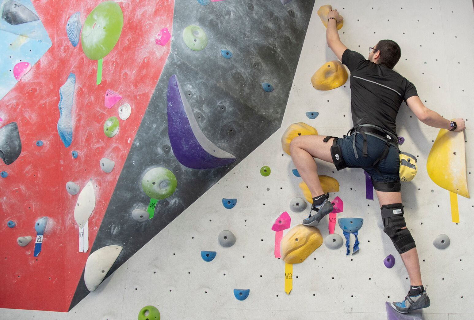 Young man hoists foot up on climbing wall.