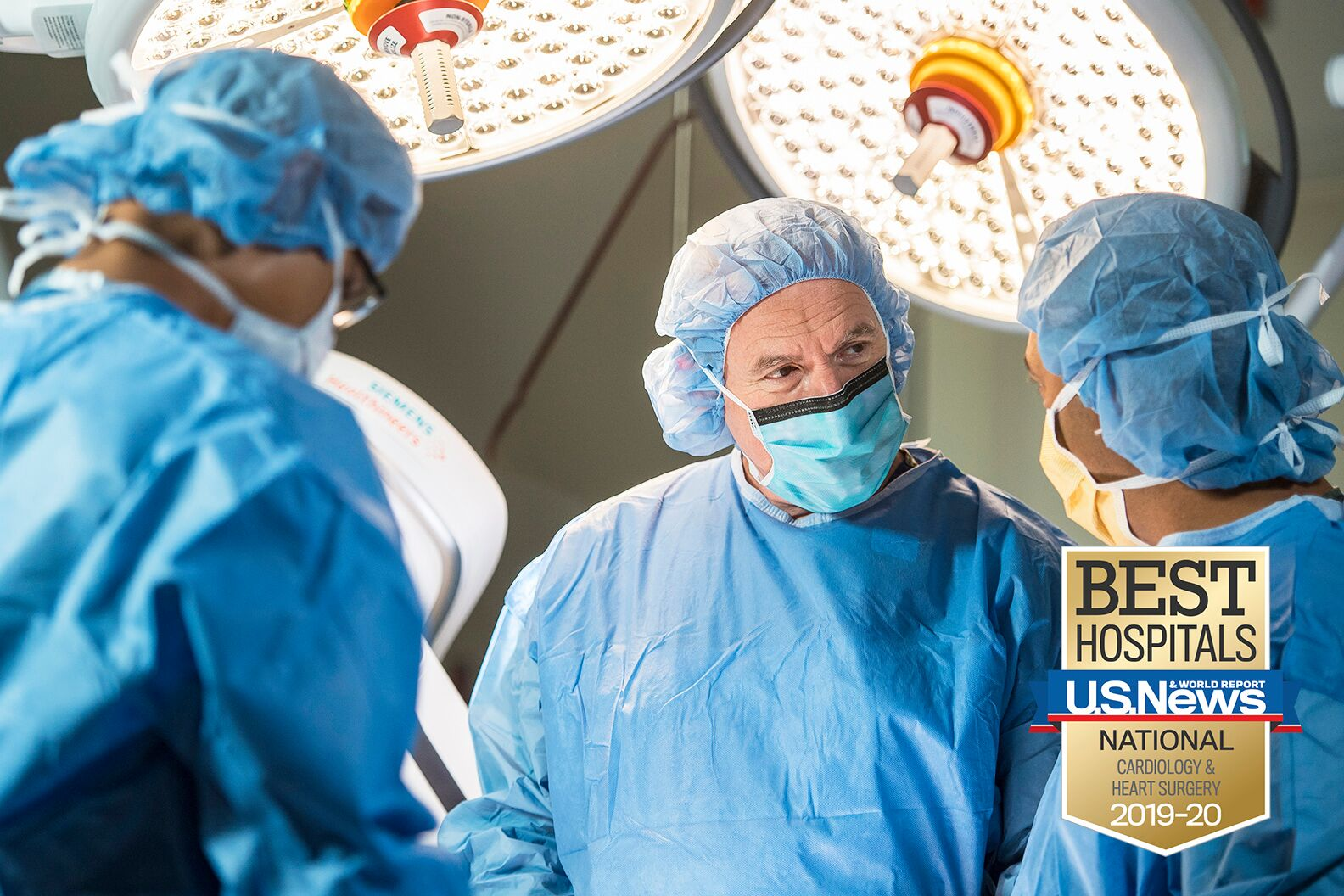 Team of doctors with sterile gowns and face masks stand in operating room over a patient who is unseen.
