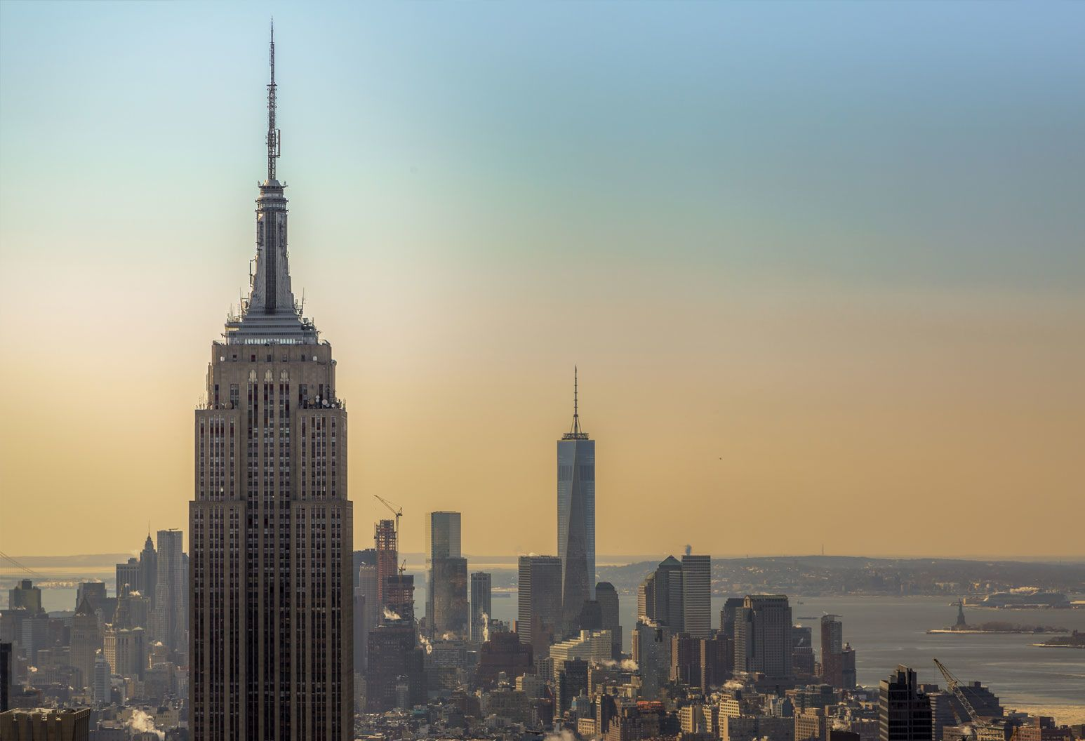 Empire state building with the New York City skyline behind it, during sunrise