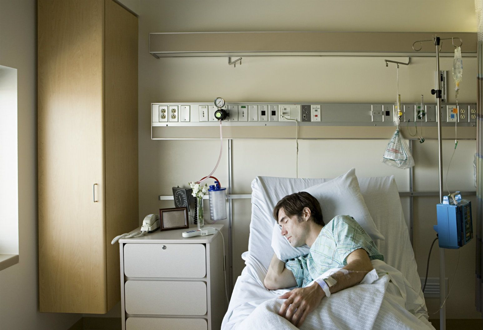 A man peacefully sleeps on his side in a hospital bed. His left arm is tucked behind his pillow, while his right arm is outstretched along his side. Light streams in from a nearby window. Northwell Health hospitals are rolling out new quiet hours and interior design changes to create a more restful patient experience.