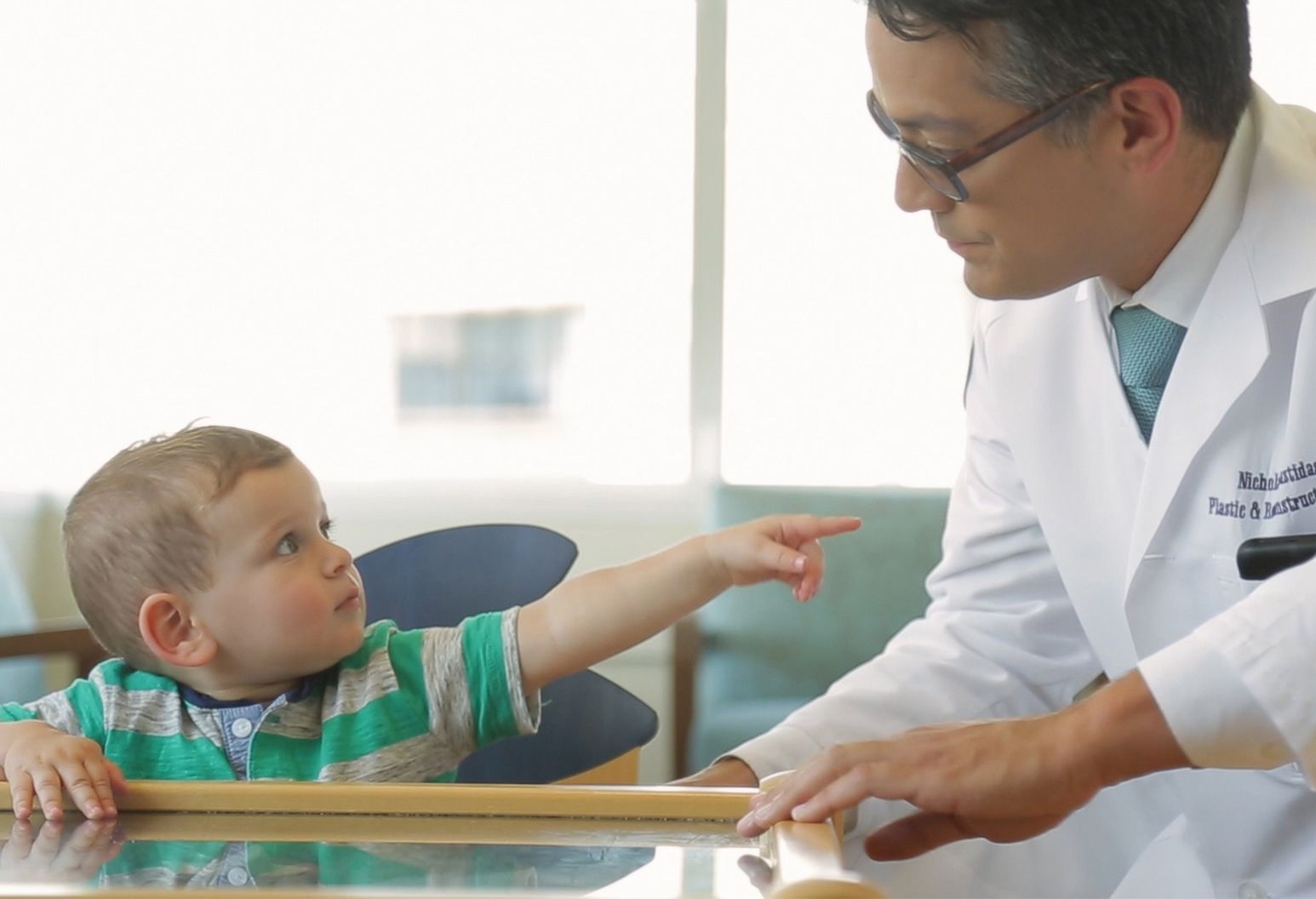 A 2-year-old boy wears a green and gray striped shirt and points and looks at a male doctor in a white lab coat, who smiles back at him.