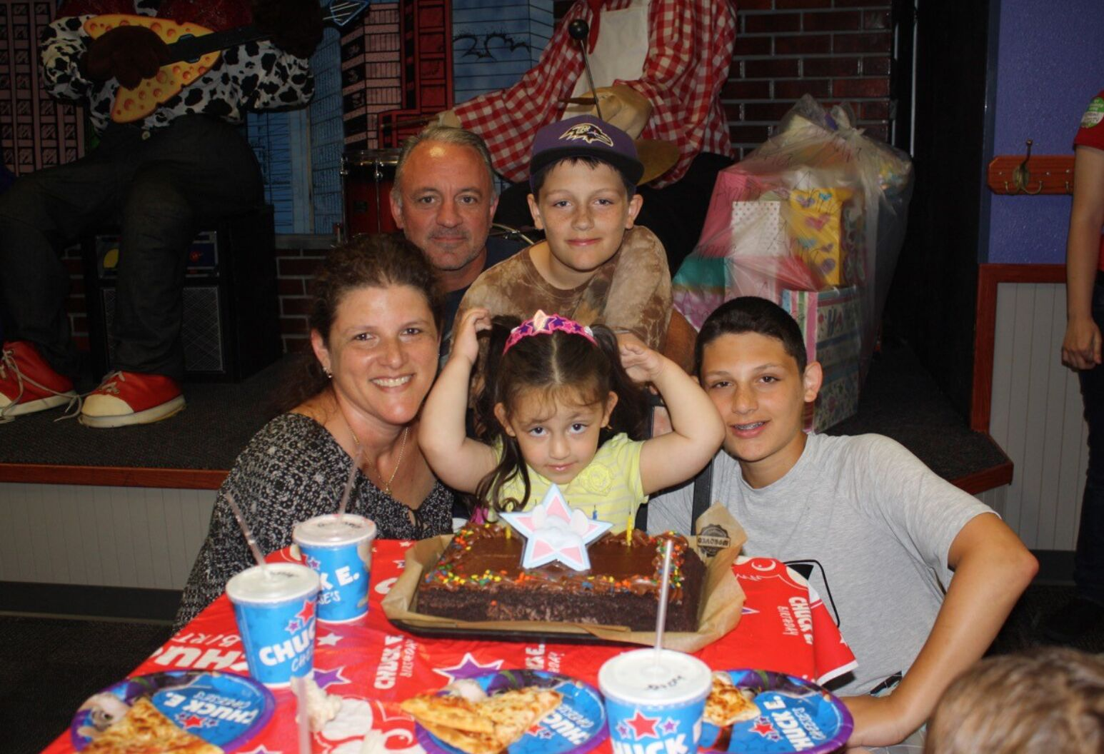 Family celebrating a birthday, sitting at a table around a cake