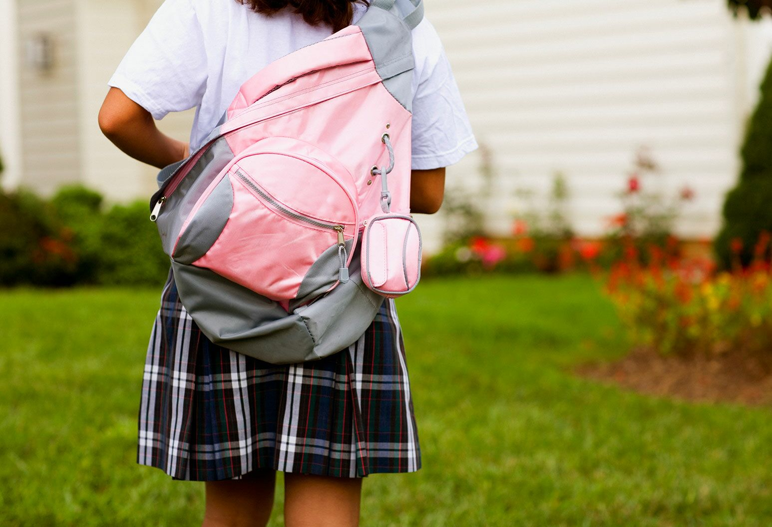 Rear view of a schoolgirl carrying a pink schoolbag