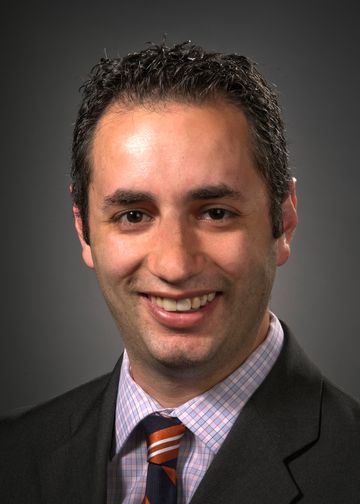 Jesse Chusid, MD, wearing a plaid shirt and blue and orange tie