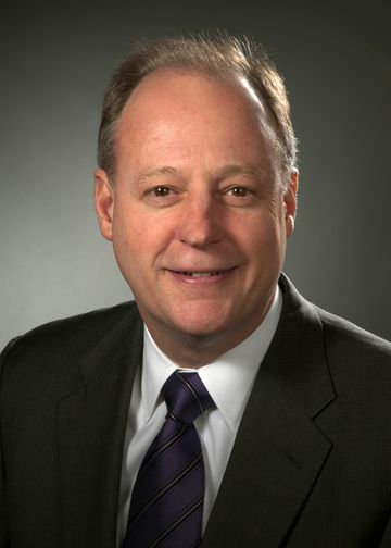 John McGovern head shot, wearing a black suit and purple tie