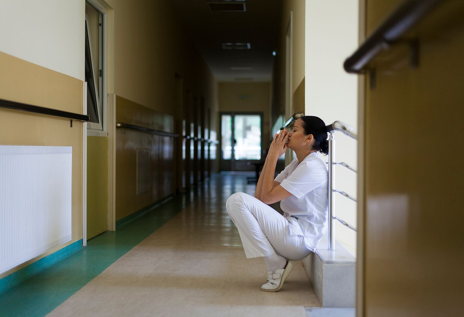 A nurse in white scrubs crouches down in a hallway looking sad.