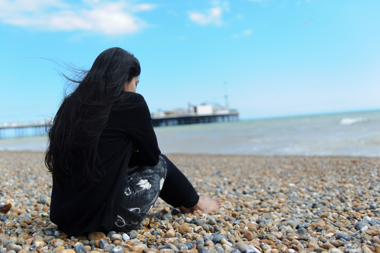 A lonely and apprehensive woman sits on a rocky beach.