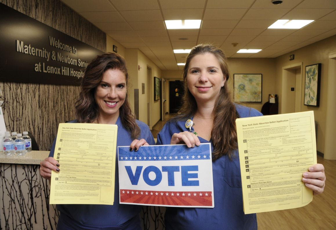 Nurses at Lenox Hill Hospital help patients fill out absentee ballots.