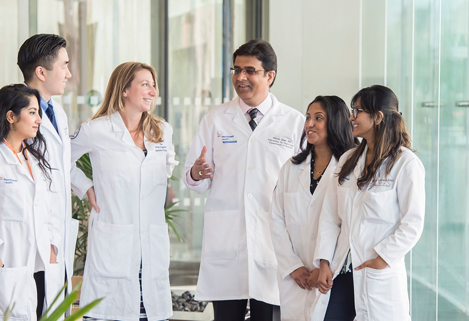 Six physicians wearing white lab coats having a positive conversation.