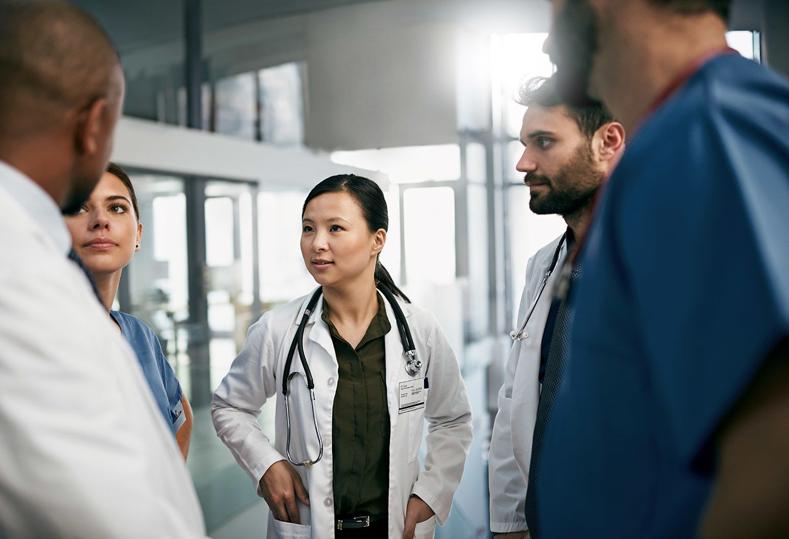 A team of doctors stand in a circle discussing a case. The focus is on a young asian female doctor wearing a dark shirt, white lab coat, and stethoscope around her neck.