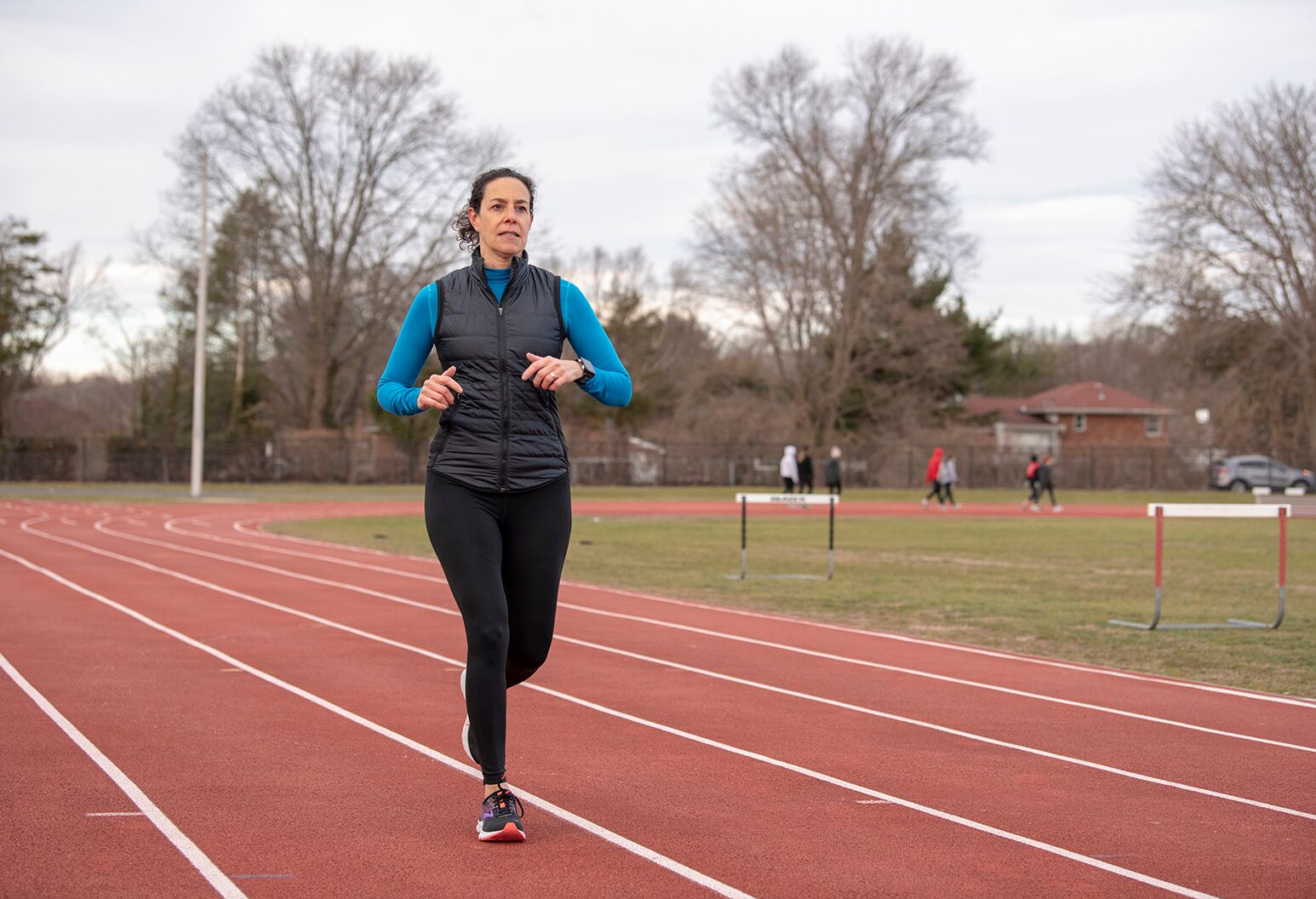 A middle-aged woman running the track