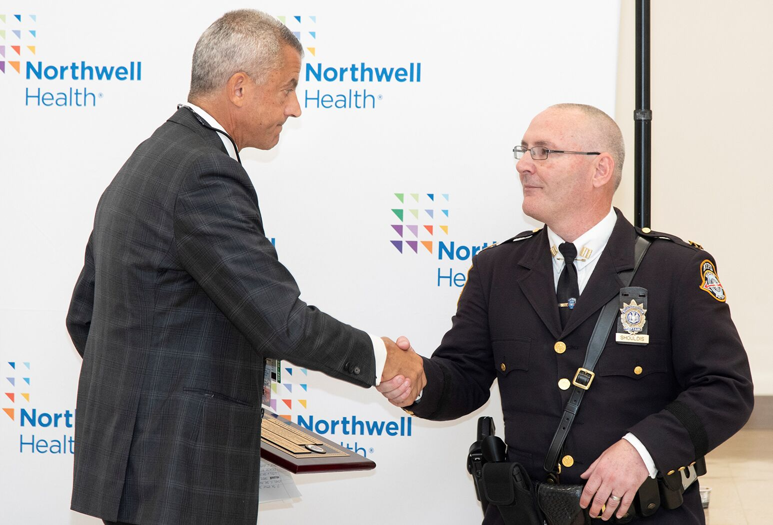 Police Captain Daniel Shouldis, NYPD Highway Patrol Unit 2, presents Dr. Joseph Marino (left) with a thank you plaque.