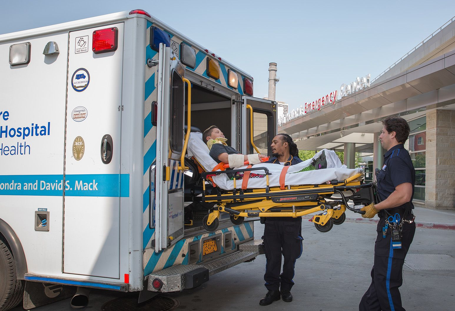 Two emergency medical services professionals lift a boy on a gurney out of an ambulance. They are in front of an emergency department of a hospital.