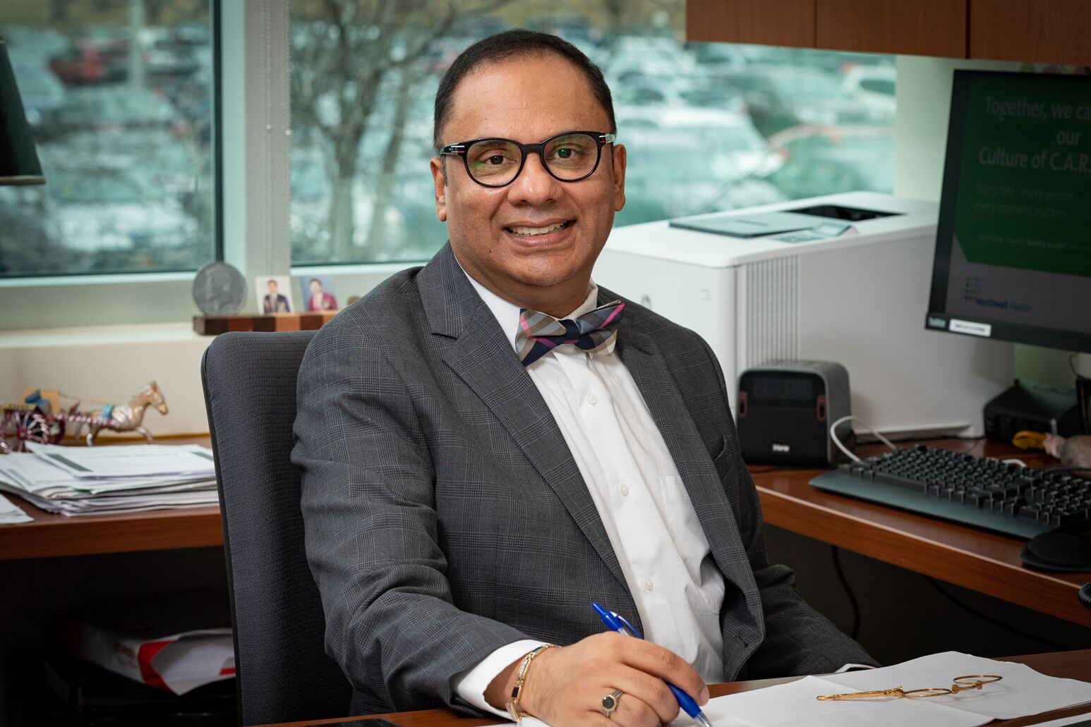 Wasif Saif, MD, sits at a desk in his office. He is the new deputy physician-in-chief and director of medical oncology for the Northwell Health Cancer Institute