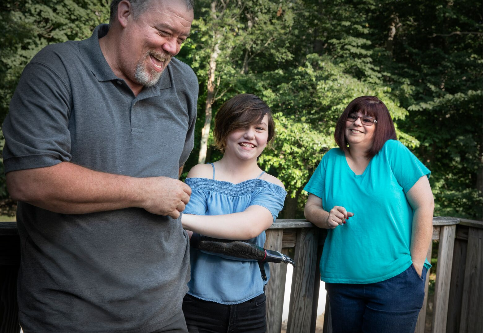 Teenage girl with a bionic arm, laughing on her porch with her mother and father