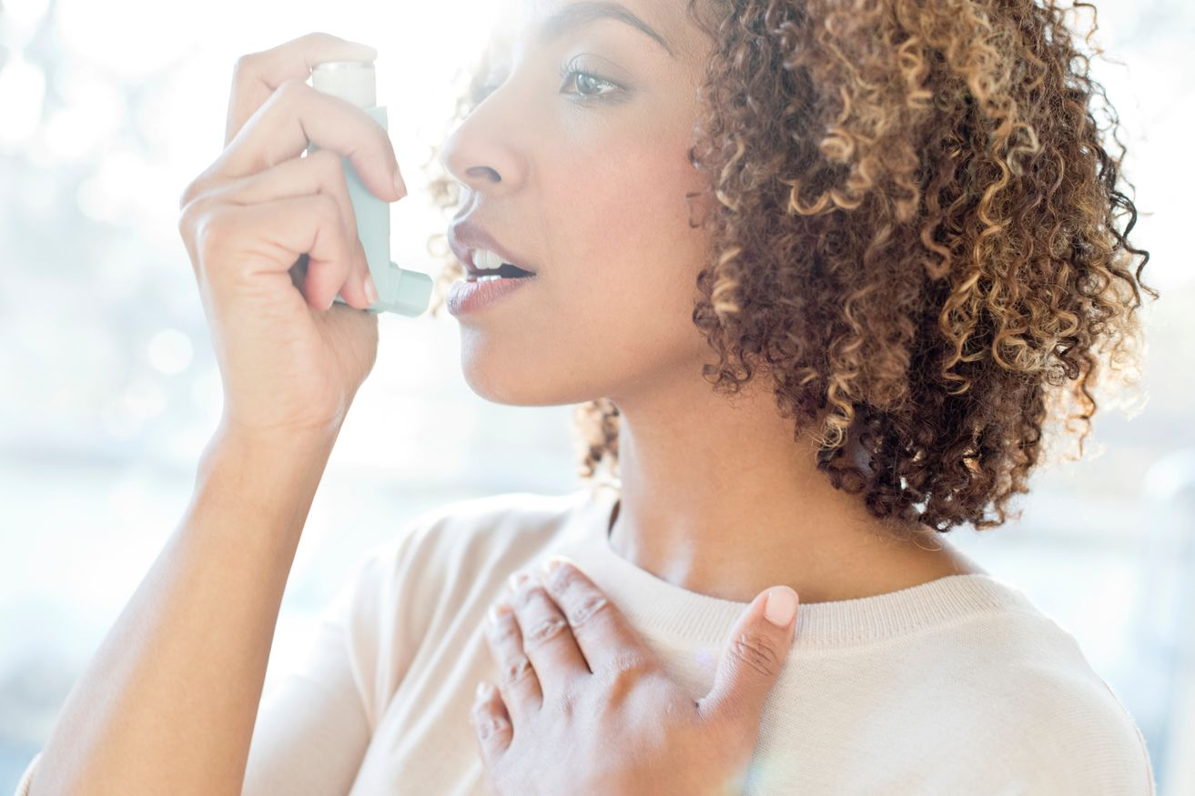 A woman takes in an inhaler