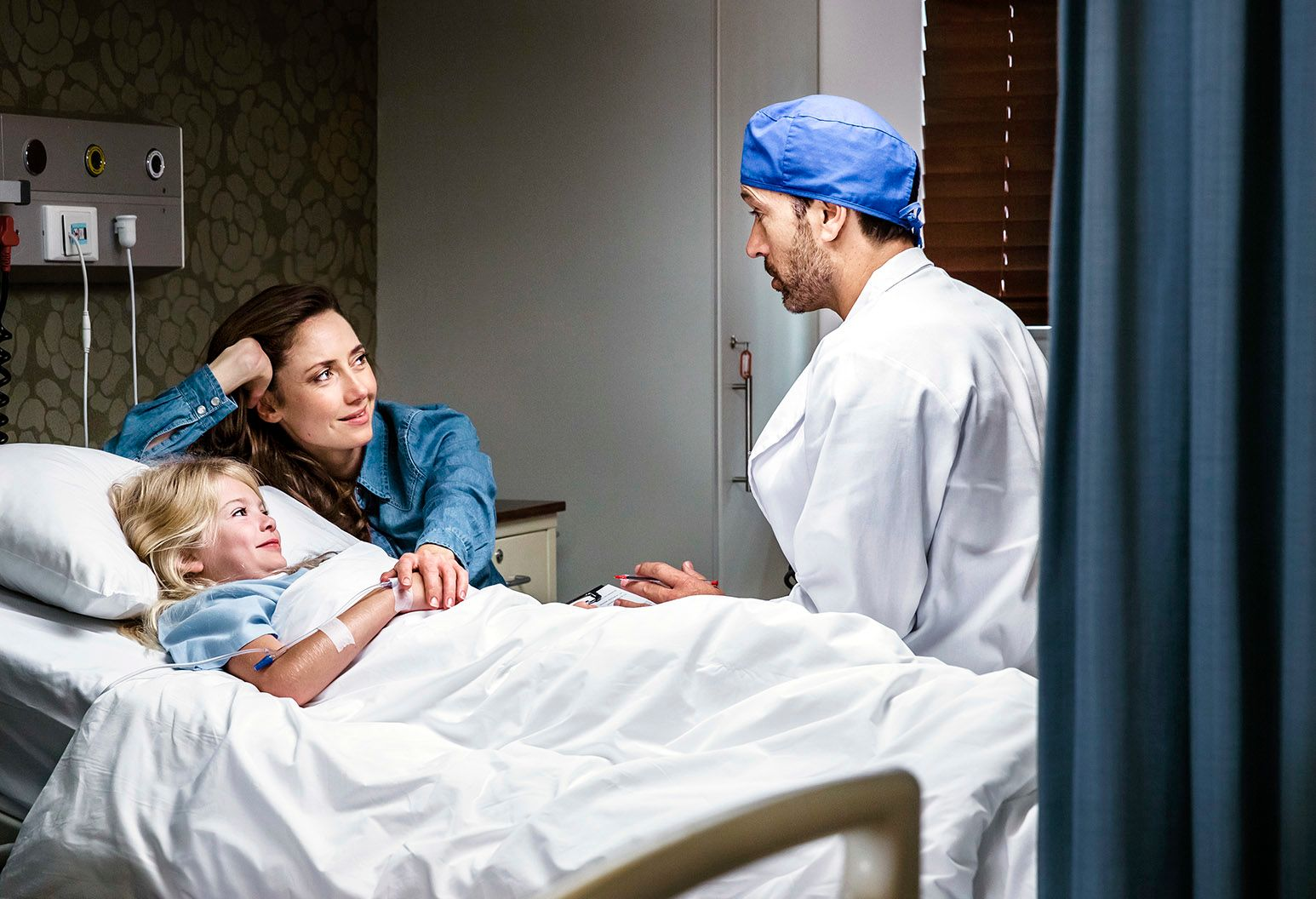 A little girl with blonde hair lays in a hospital bed and her mother is next to her holding her hand. A male doctor wearing a blue operating room cap is also beside, talking to them.