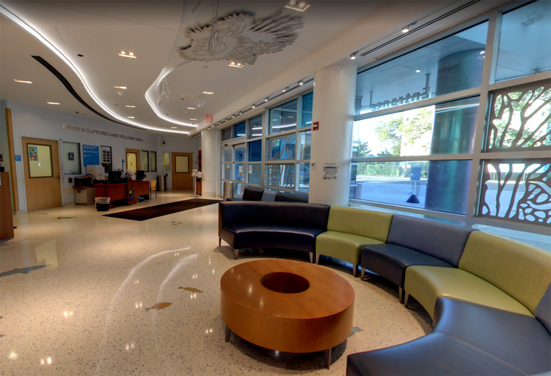The brightly lit lobby of the emergency department showcases a large, colorful couch in the shape of a semi-circle and an oval wooden coffee table at center.