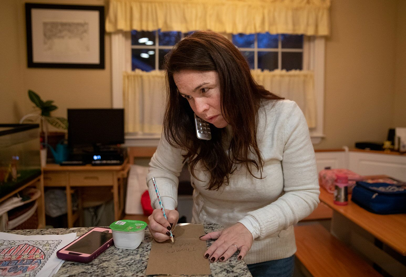 A woman with long auburn hair in a white sweater, stands by a countertop holding a phone to her ear with her shoulder as she writes on a cardboard cutout with a pencil.