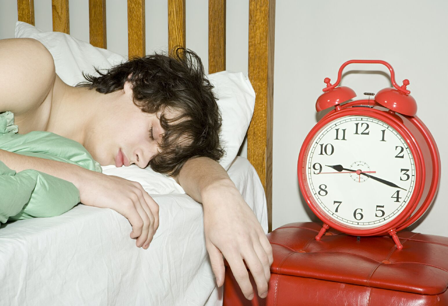 A boy sleeping in bed next to a red alarm clock