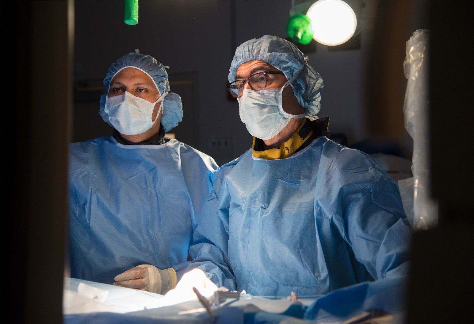 Two surgeons are wearing surgical gowns and masks are in the operating room looking at a monitor