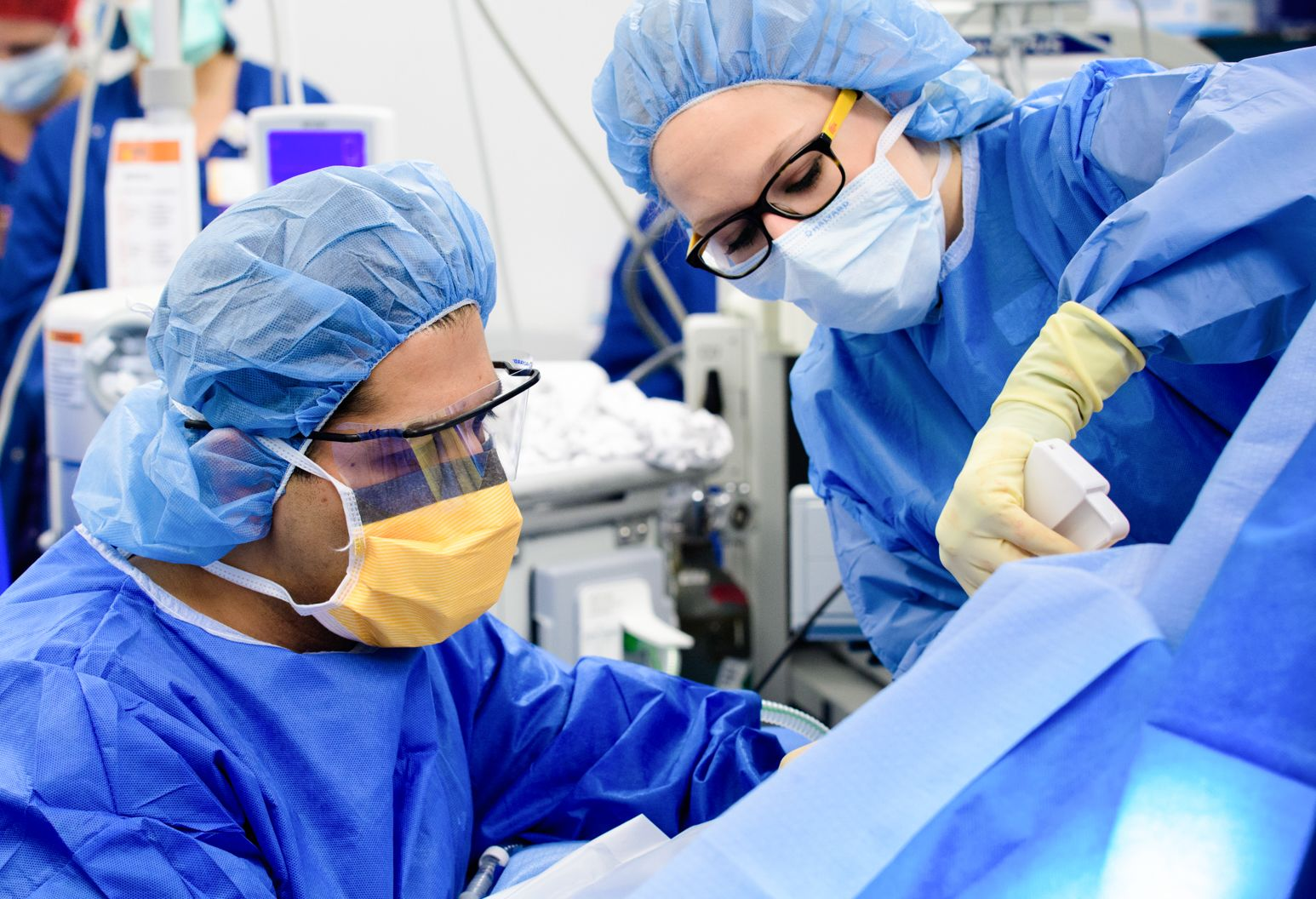 Male and woman in blue scrubs and protective face gear operate on someone under a blue cloth.