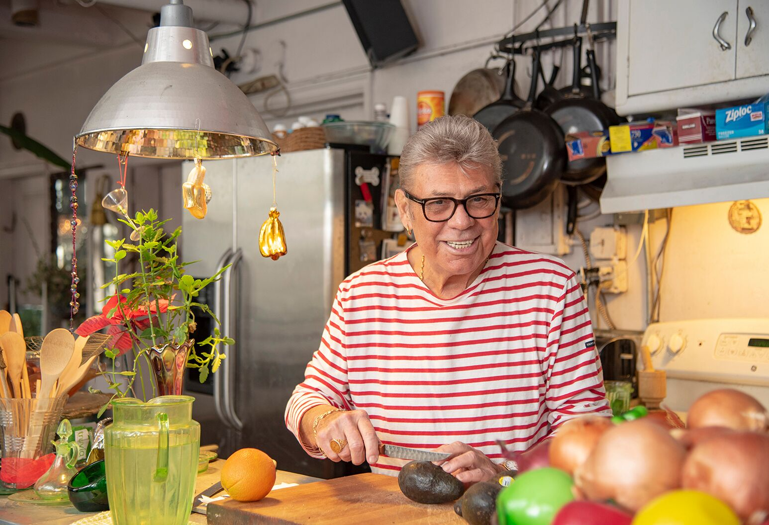 A smiling man in his late 70s slicing an avocado in his kitchen