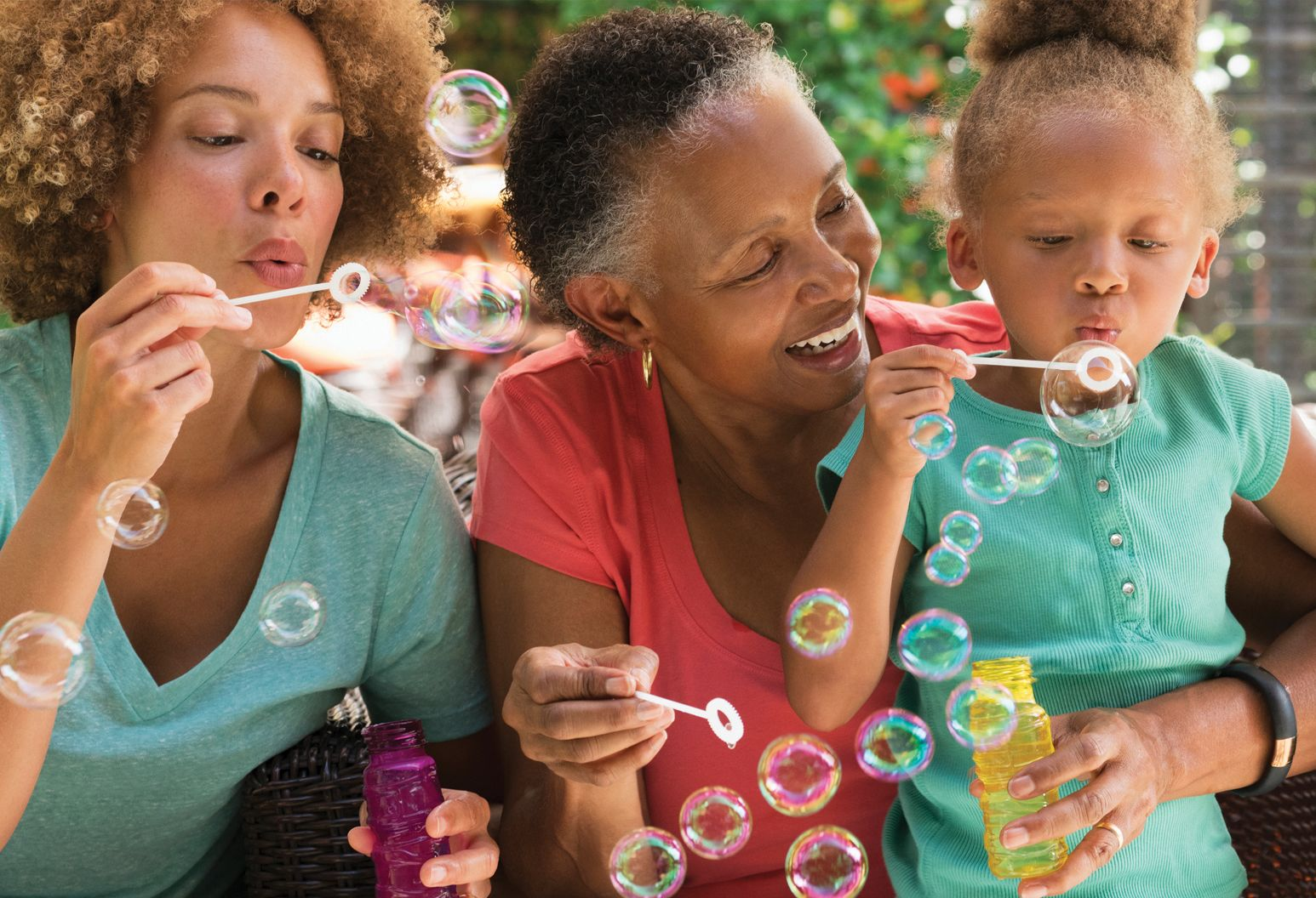 Three generations of women, grandmother in red shirt and mom and 5-year-old daughter in matching green shirts, blow bubbles together.