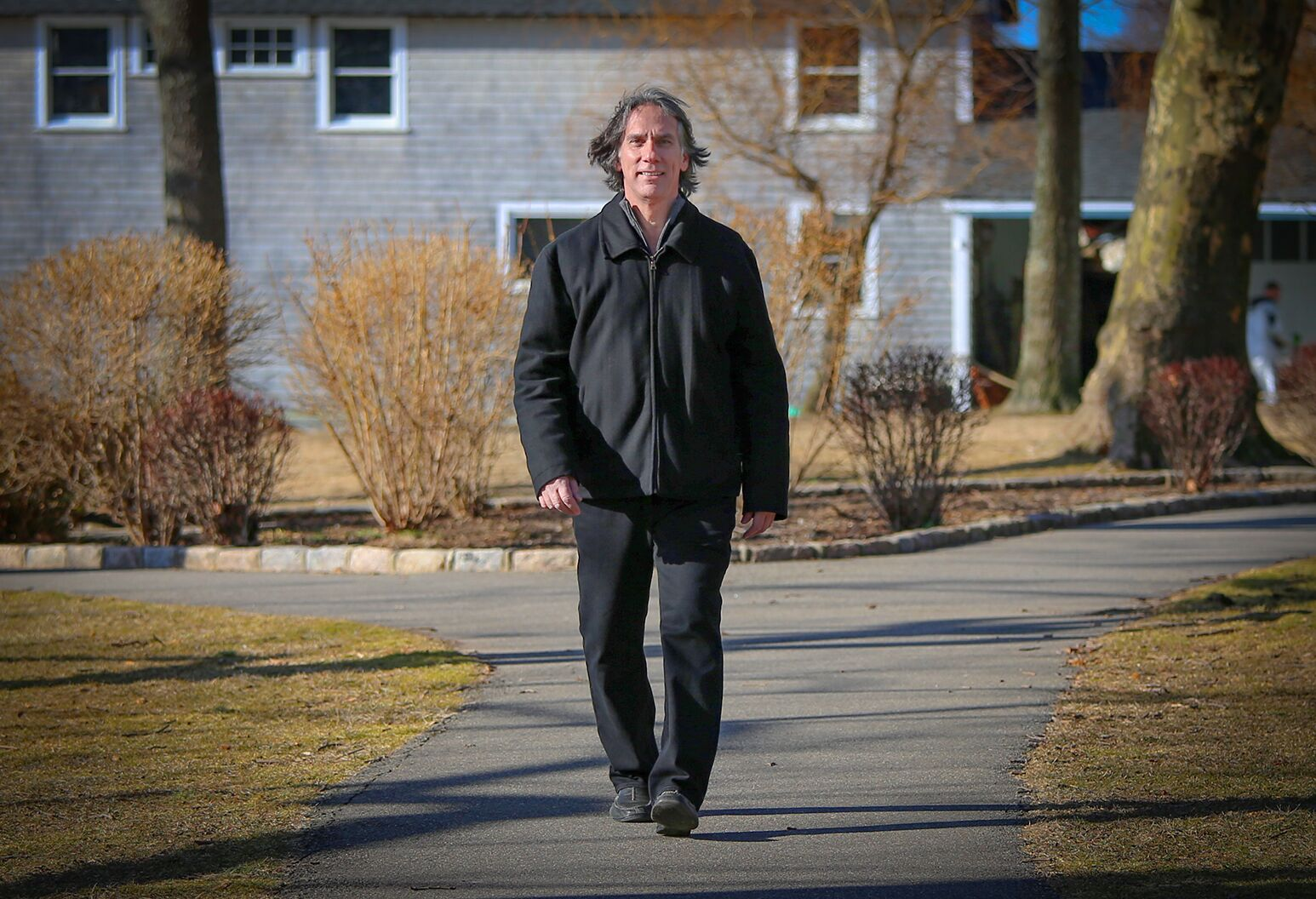 Man in his 60s walking outside on sunny day.