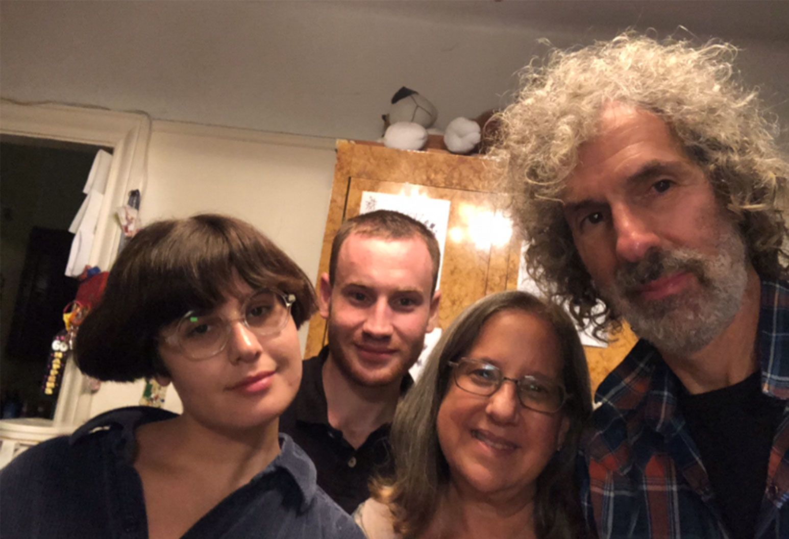 A group of people pose for the camera. An older man with grey hair and a scruffy beard, an older and younger female both wearing glasses, and a young man with short hair.