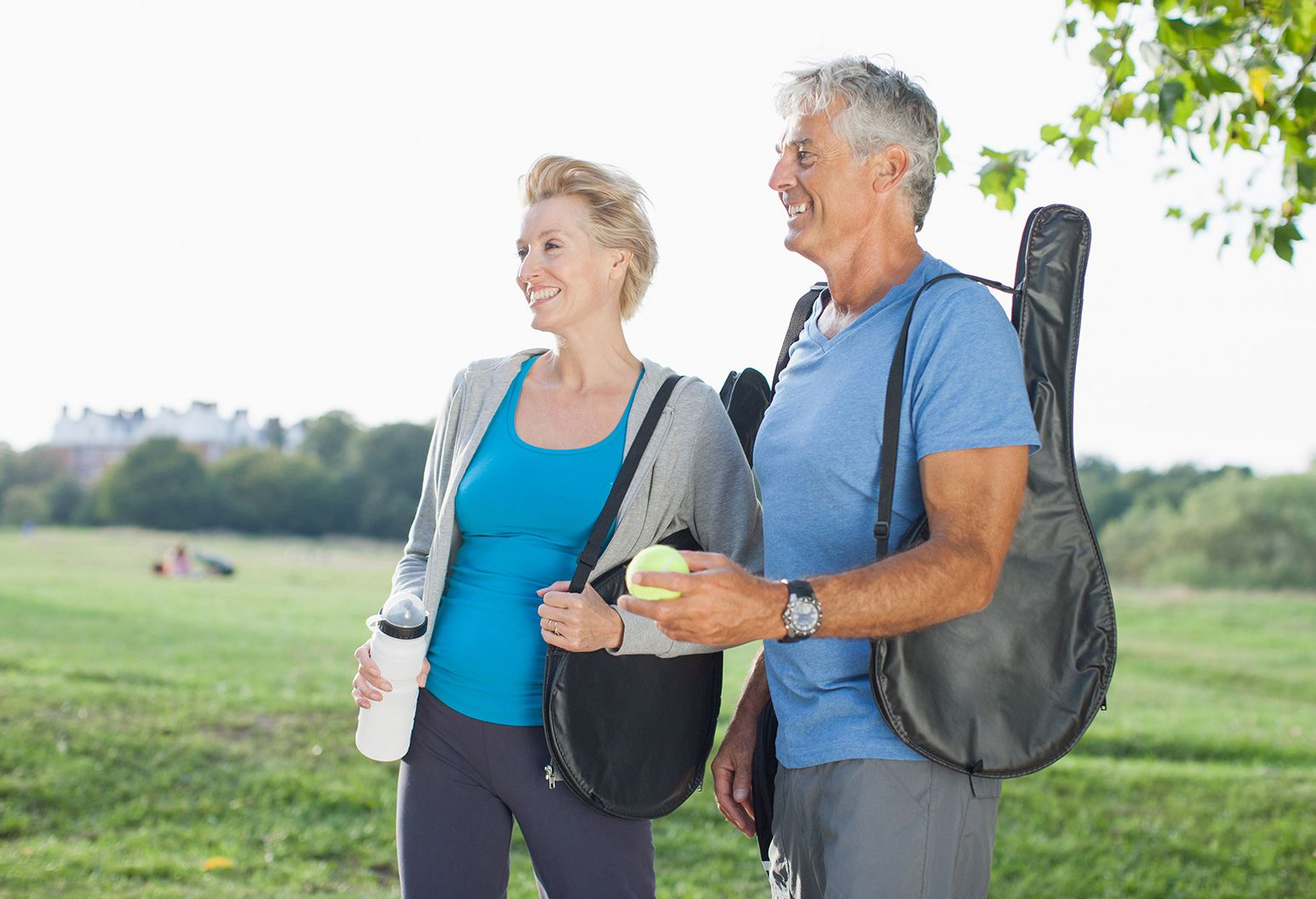 Middle-aged couple, smiling, standing in a park with tennis racquet bags on their shoulders
