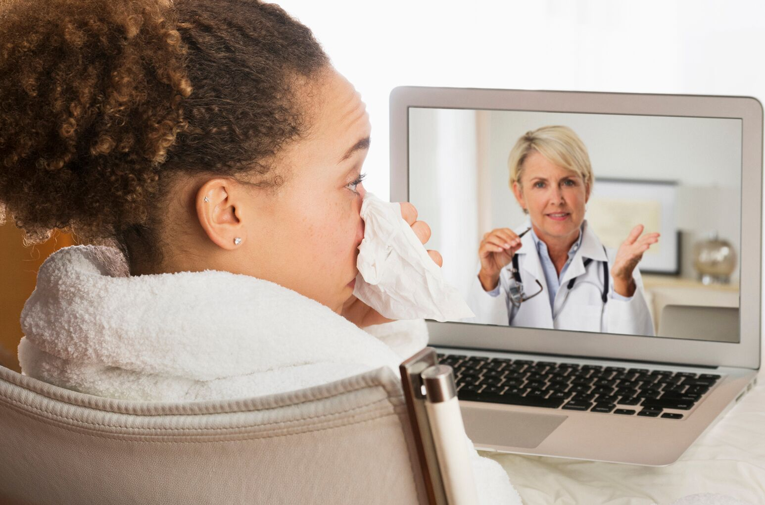 A sick woman talks to a doctor through a telehealth services device.