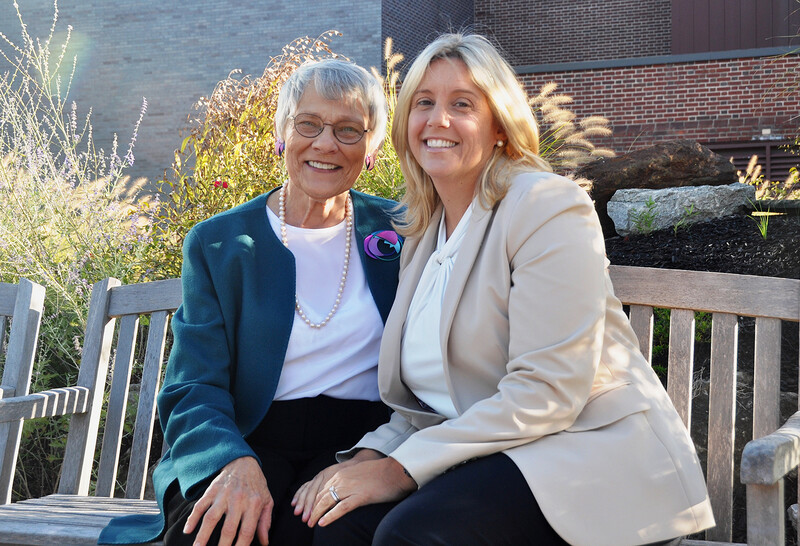 Judith A. Jedlicka, founder of the Caregivers Center at Peconic Bay Medical Center, and Tara Anglim, LCSW-R, director of patient and family-centered care at Peconic Bay Medical Center, pose outside, sitting on a bench.