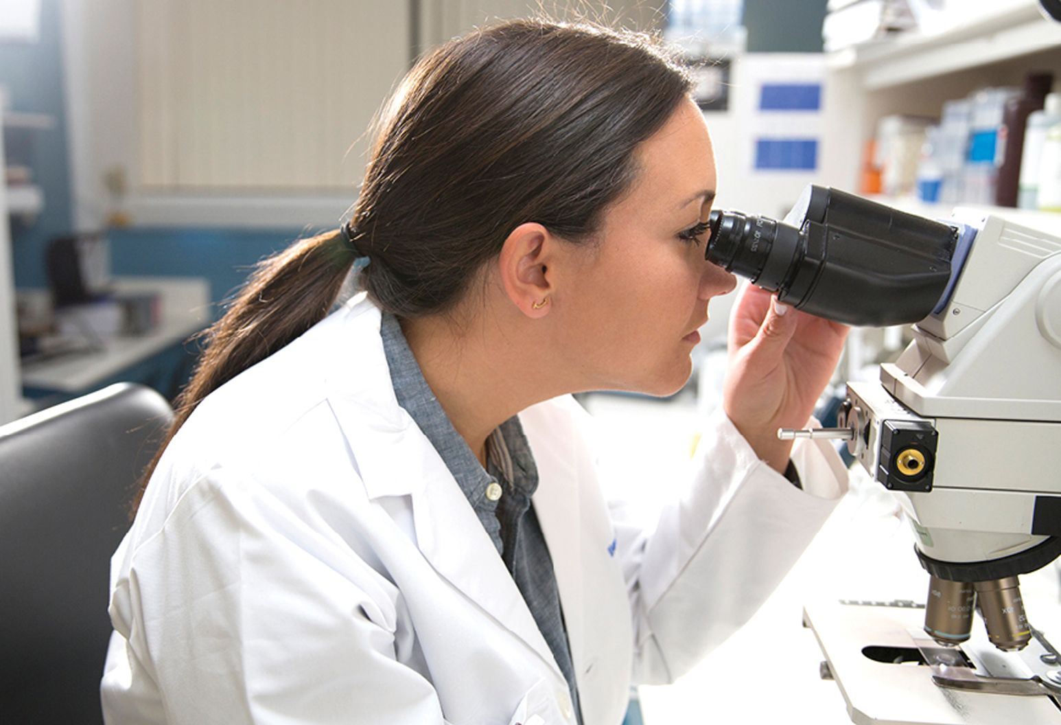 female physician looking into microscope