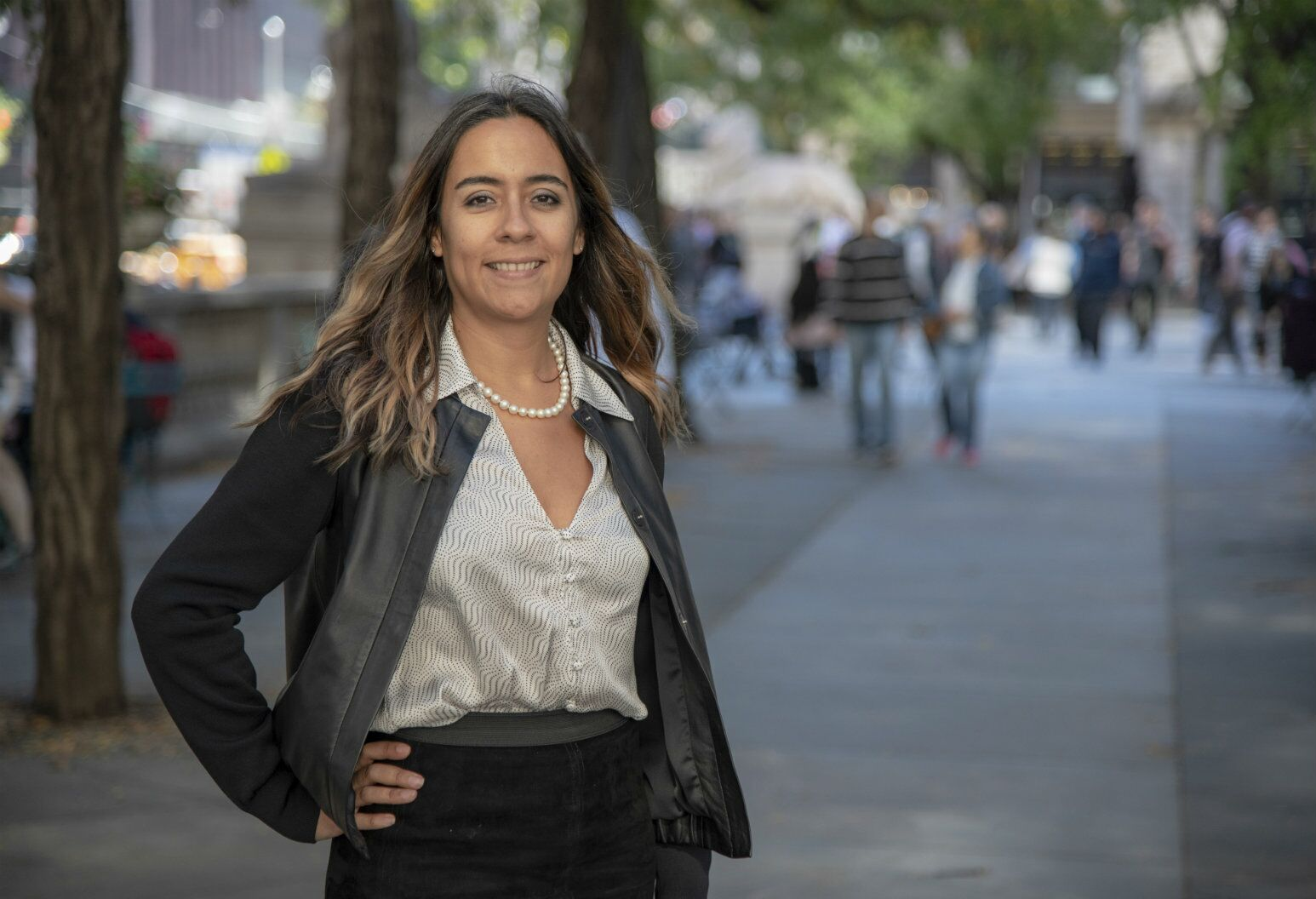 Liliana Uruburo poses on a city sidewalk in professional attire. Ms. Uruburo feels confident in her health because of the BRCA Center's specialists.