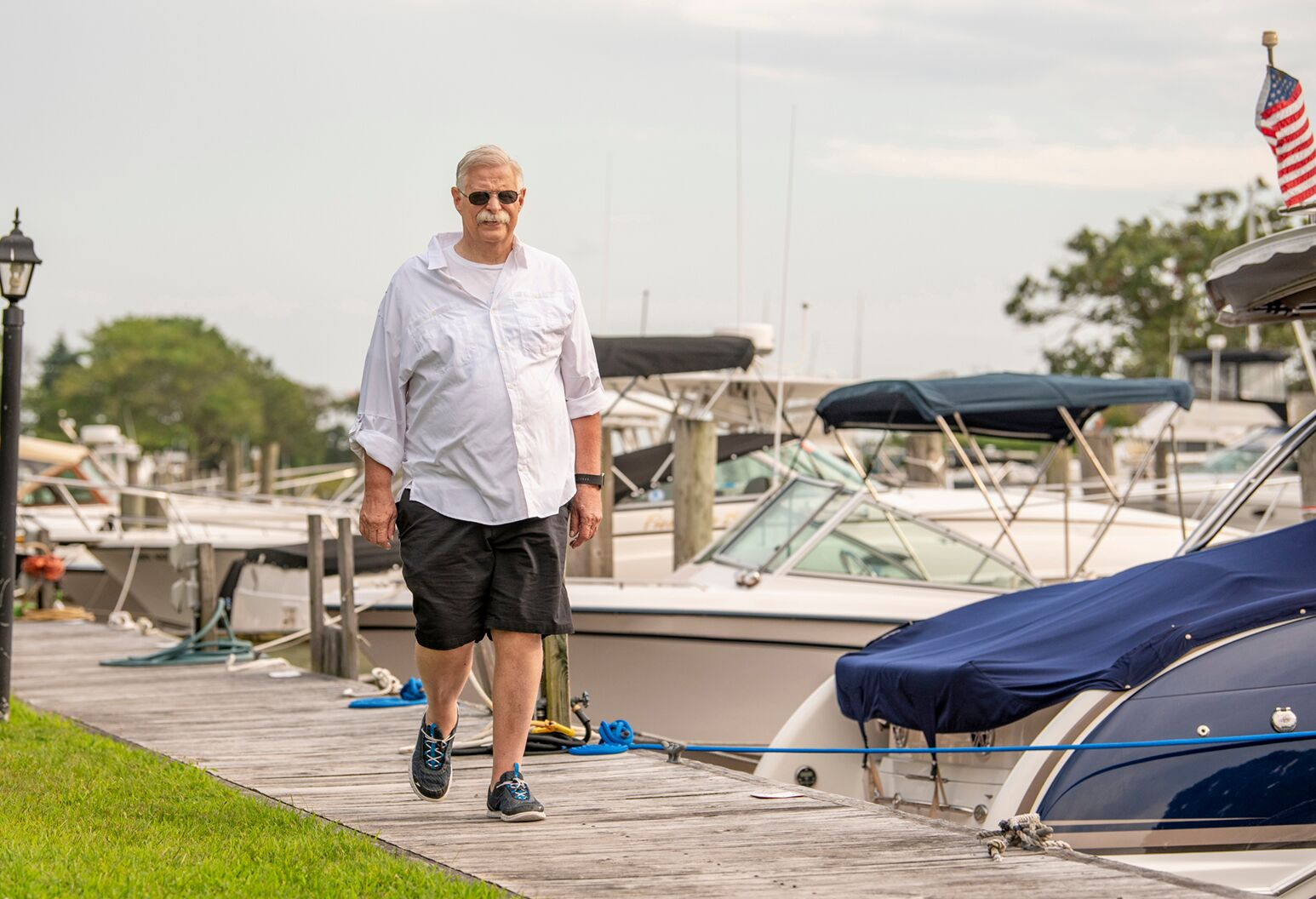 Man in his 60s walks on a dock next to tied-up boats.