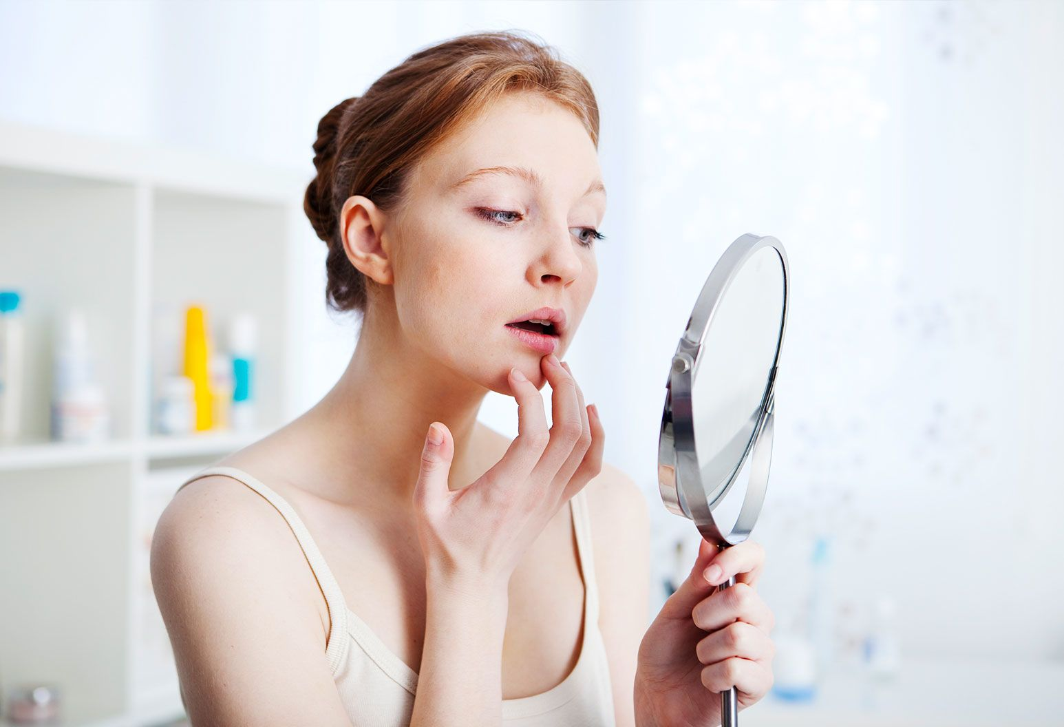 A young woman with red hair and a white tank top is in her bathroom looking into a mirror. Her finger is gently touching her lip and her other hand is holding a silver mirror.