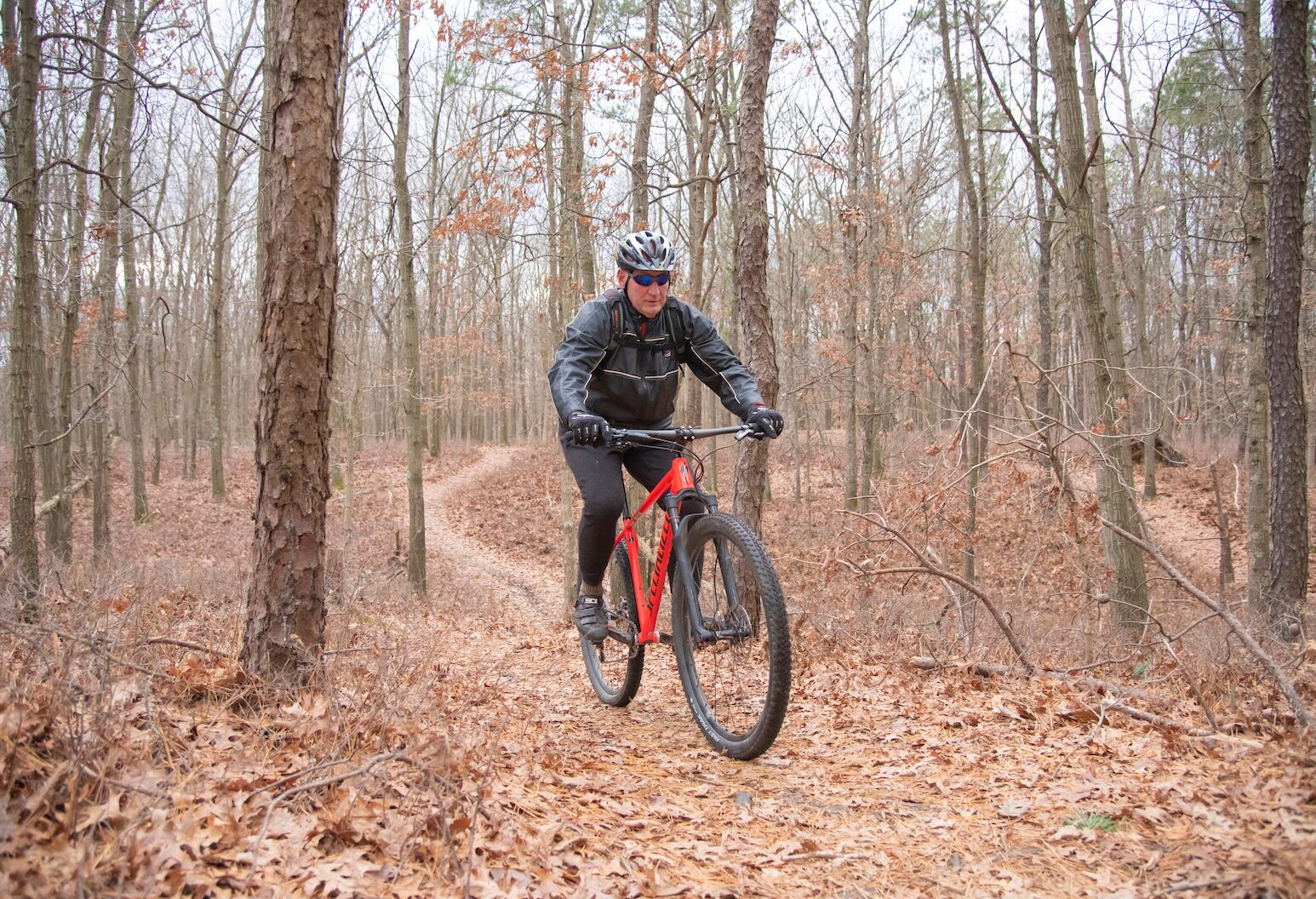 John Krafinski rides his bike in the woods.