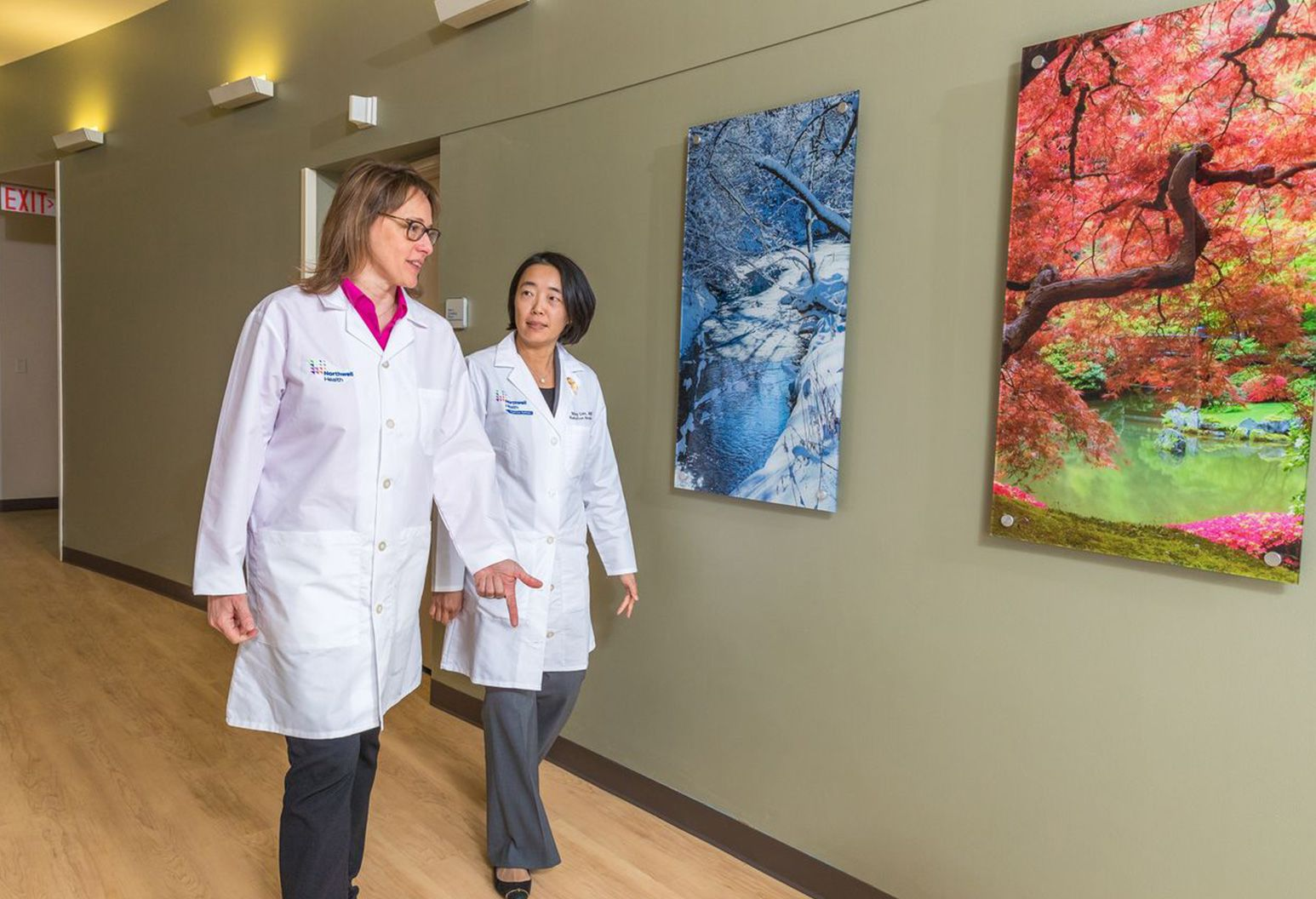 Two female doctors wearing white lab coats are walking and talking in a hallway with blue and pink artwork on the wall.