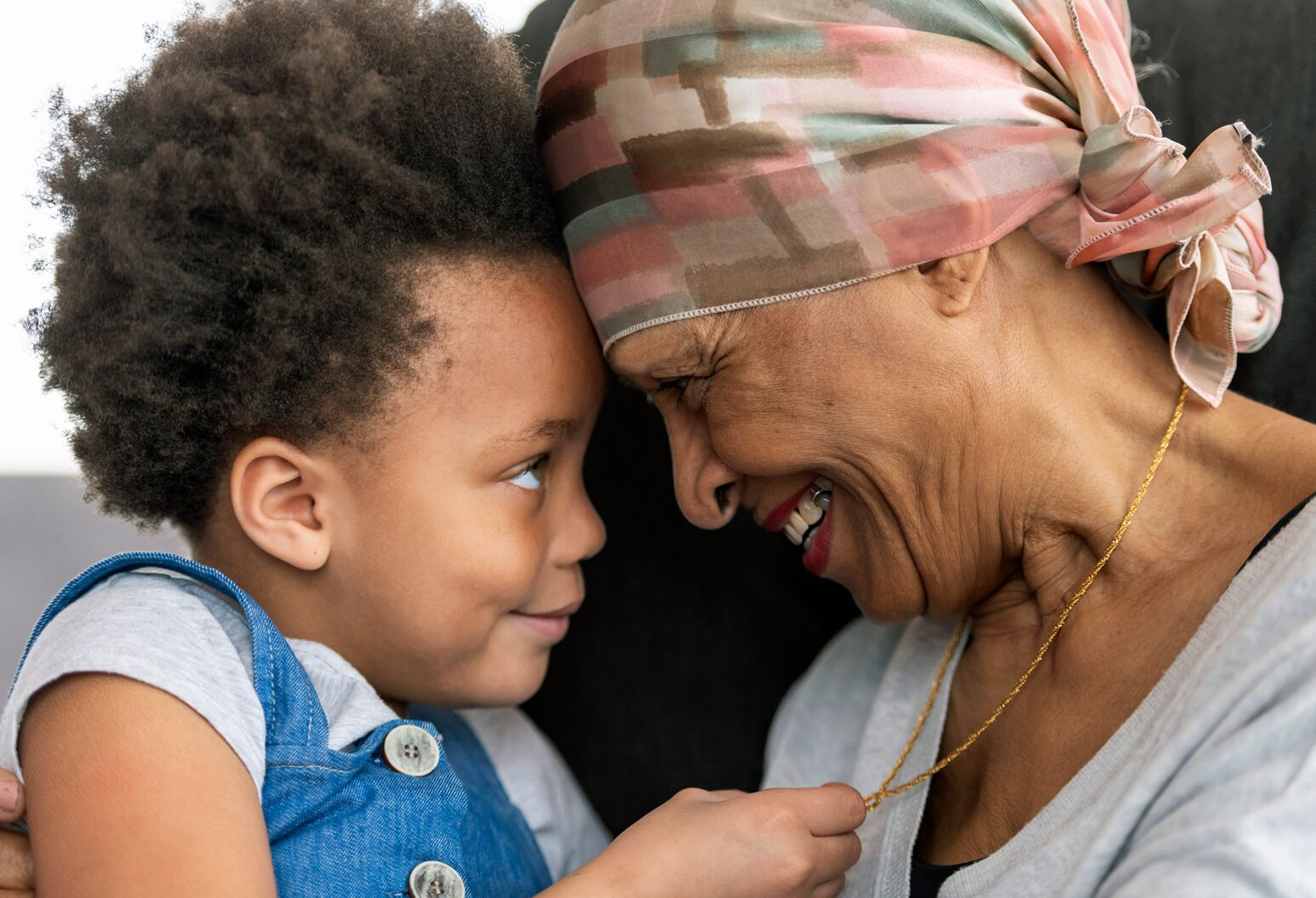 A child grabs her grandmother's necklace. The grandmother is wearing a scarf on her head after losing her hair during pancreatic cancer treatment.