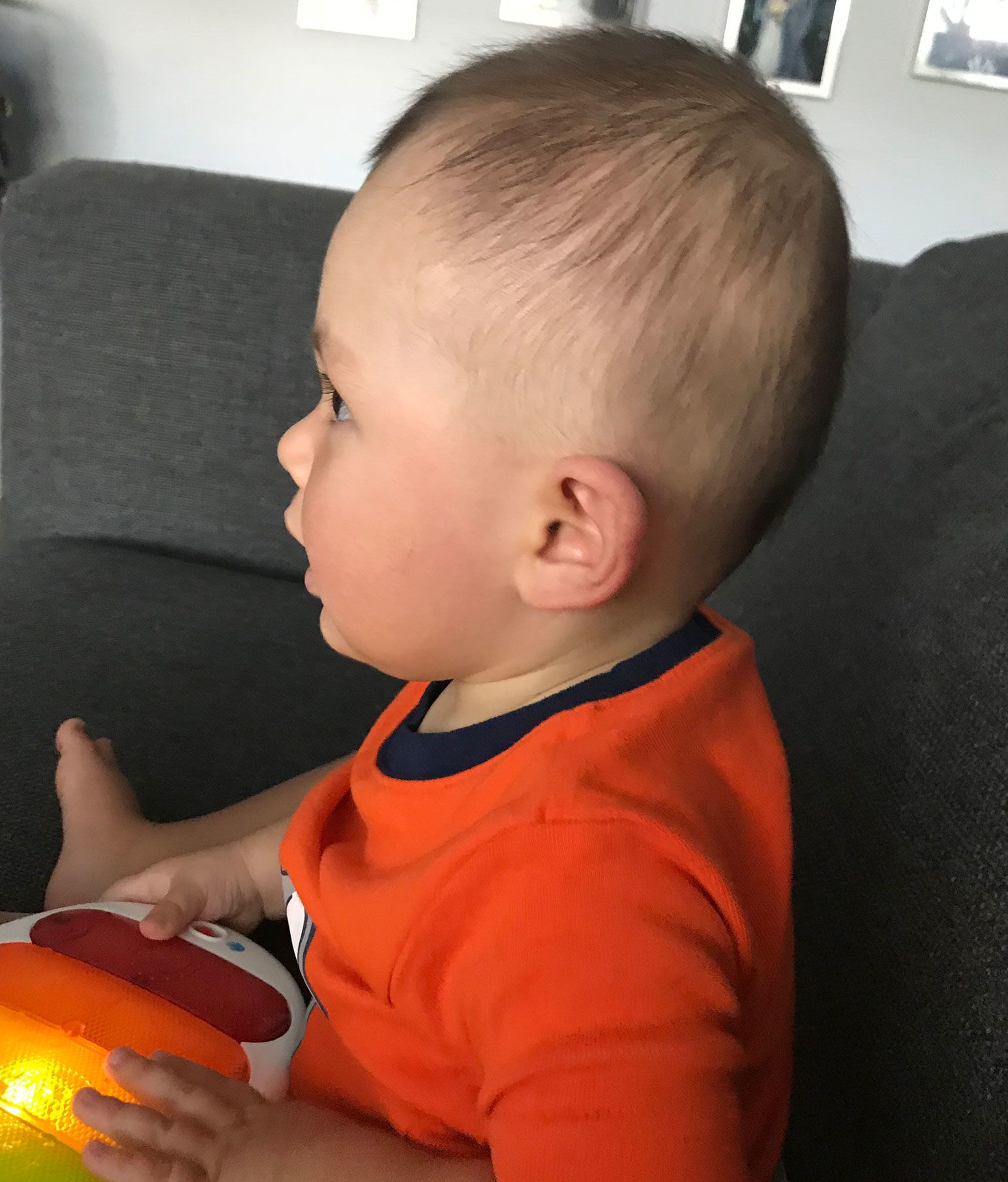 Side profile of a baby sitting on a couch playing with an electronic keyboard. His head is shaped round.