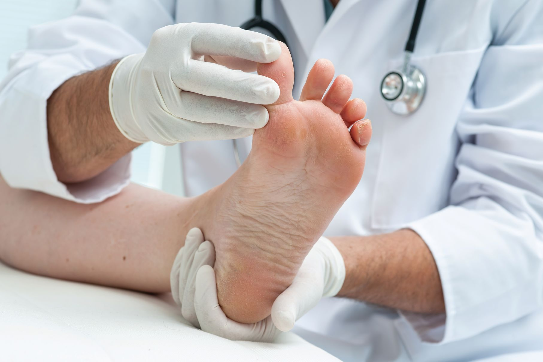 A podiatrist looks at a foot