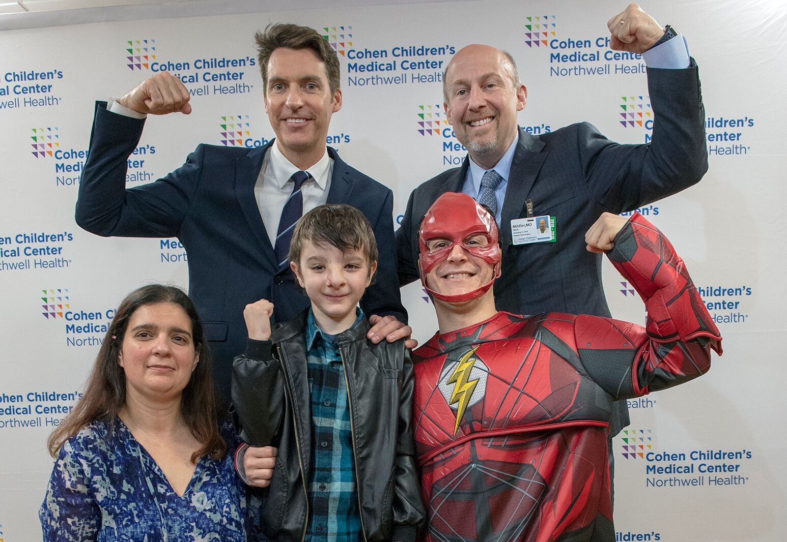 From left: Dr. James Bradley and Dr. Mark Mittler celebrate Simao's return to school with his mom, Lisa, and favorite superhero, the Flash.
