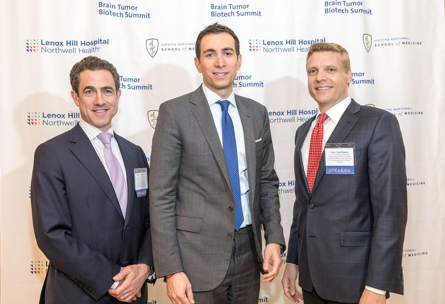 Three male doctors wearing suits are standing in front of backdrop that shows the Lenox Hill Hospital and Hofstra/Northwell School of medicine logos
