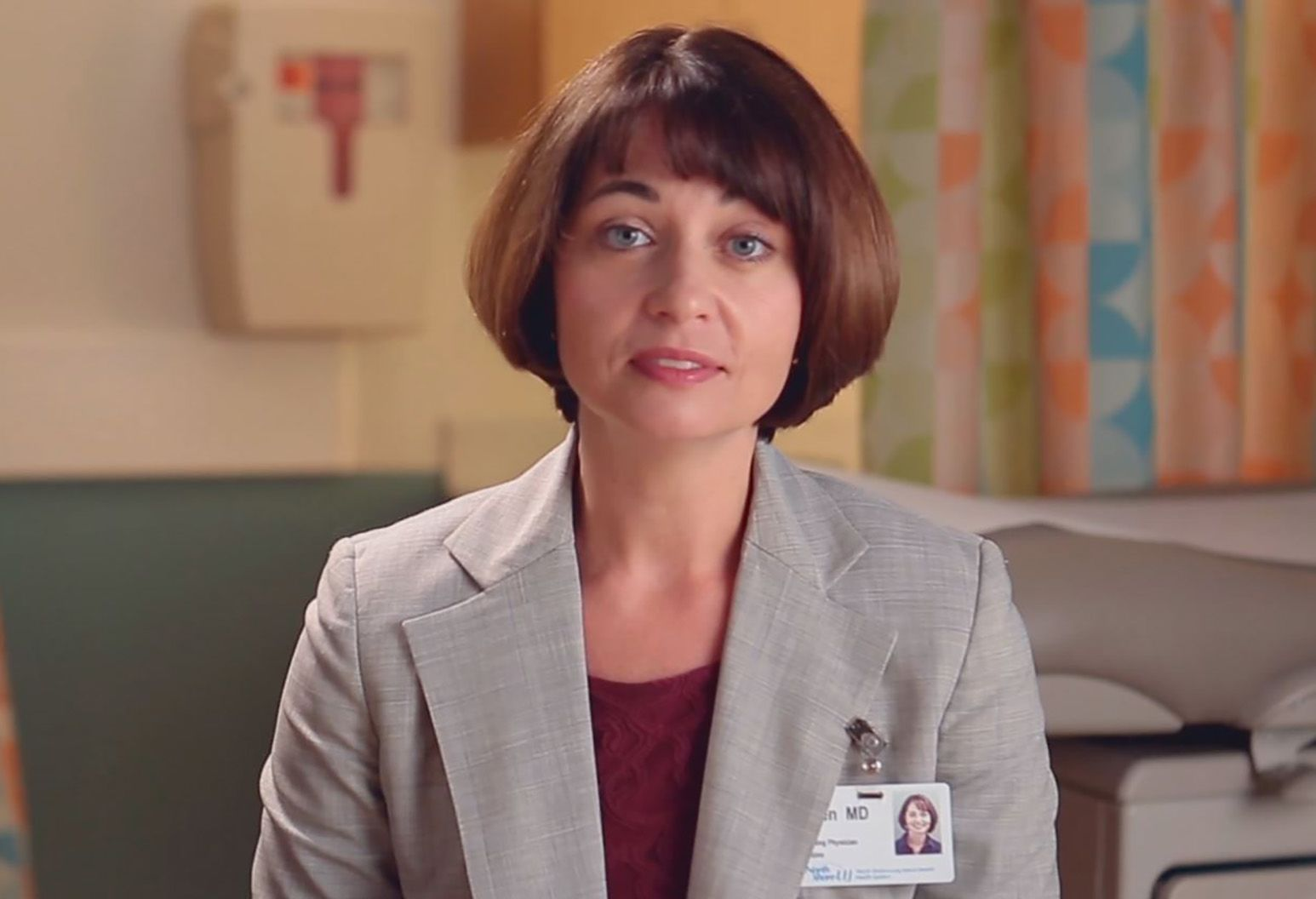 A lady with short brown hair and bangs is in between words. She wears a gray suit jacket and wears a Northwell Health badge.