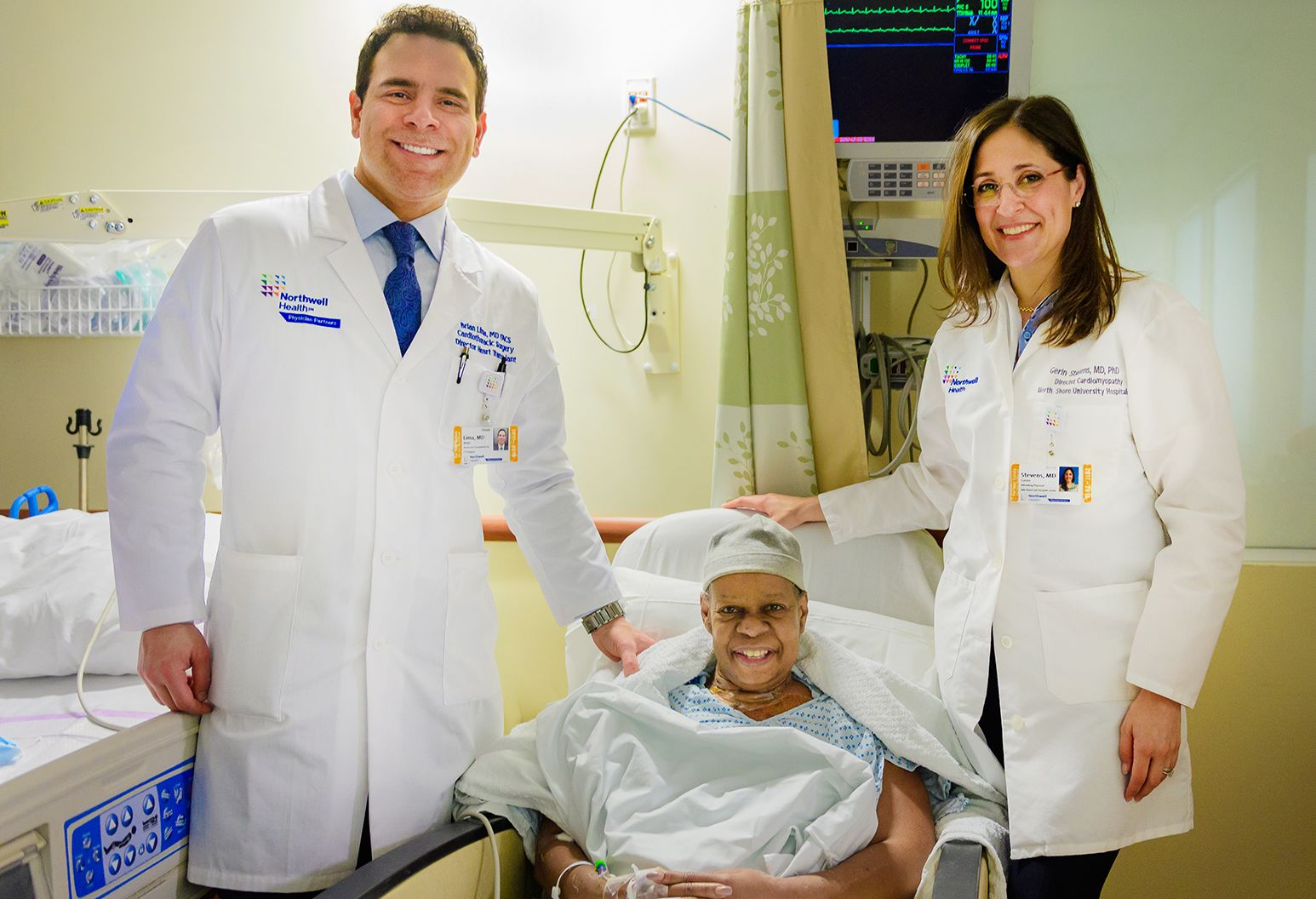A woman sits in a hospital chair wearing a hospital gown and a grey cap. She has a white sheet wrapped around her. To the left stands a man in a button down shirt, tie and white lab coat. To the right stands a woman with glasses and a white lab coat.