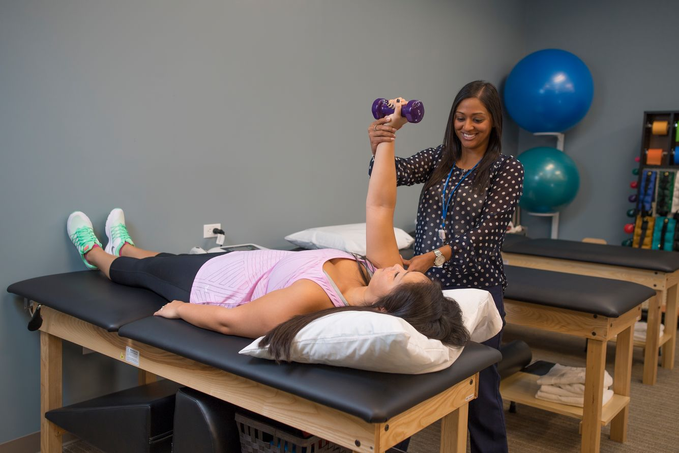 Physical therapist working on an arm movement with a patient to help strengthen the muscles.